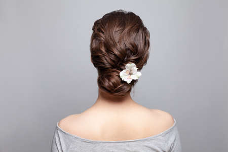 Beautiful woman back and head with perfect hairdo and white flower on white background