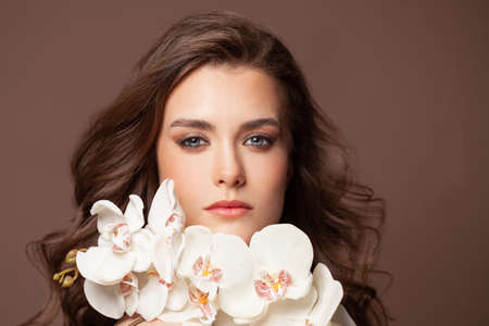 Beautiful female face with healthy brown hair, clear skin and white orchid flowers portrait