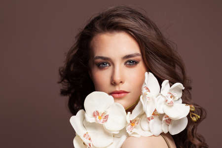 Perfect female face with healthy clear skin and white orchid flowers portrait. Facial treatment and skin care concept