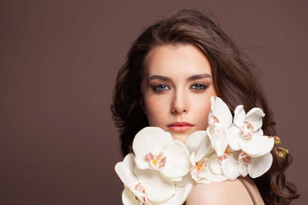Young pretty woman face with healthy clear skin and white orchid flowers portrait. Facial treatment and skin care concept
