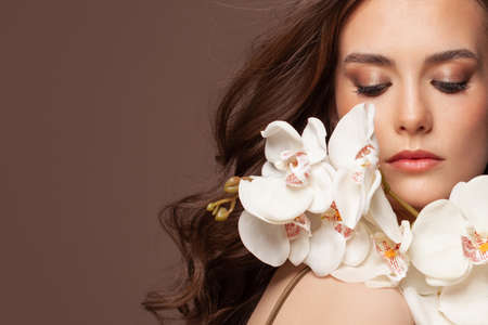 Nice female face with white orchid flowers portrait 写真素材