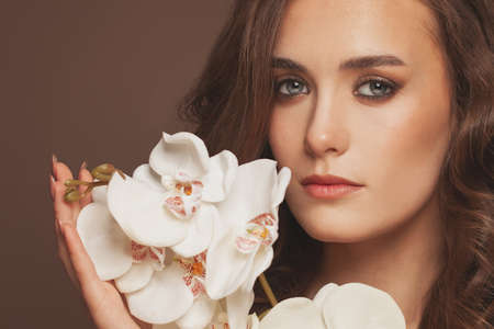 Young perfect woman face with white orchid portrait 写真素材