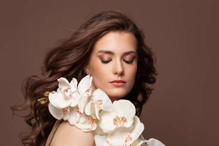 Attractive female face with clear skin, healthy brown hair, natural makeup and white orchid flowers portrait