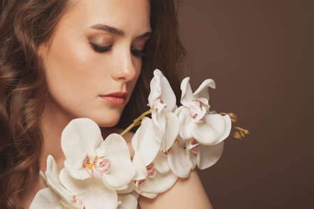 Lovely model woman with healthy clear skin and gentle orchid flowers. Facial treatment and skin care concept