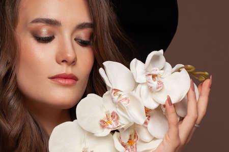 Closeup portrait of perfect woman with orchid flowers