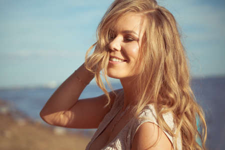 Lovely smiling blonde woman in sun light outdoor