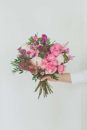 Pink, purple and green flowers in female hand on white background