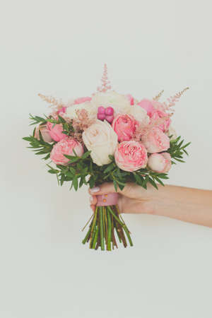 Gentle pastel pink flowers bouquet in female hand on white background 写真素材