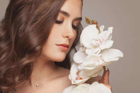 Portrait of beautiful young woman with white orchid flowers