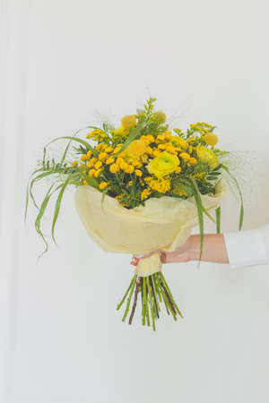 Yellow flowers and green grass in female hand on white background