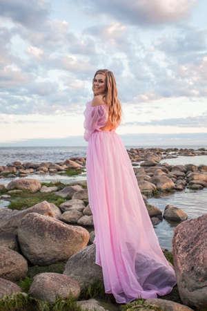 Glamorous young woman in pink dress outdoor