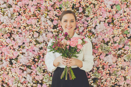 Smiling woman with bouquet of flowers on floral background