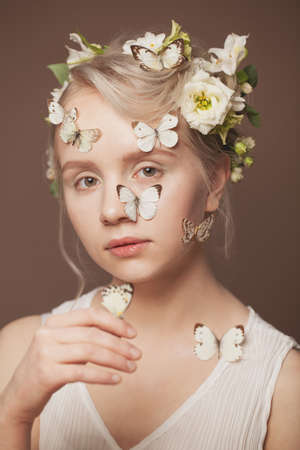 Closeup portrait of cute woman blonde model with healthy updo hairdo, white spring flowers and gentle butterfly on brown background