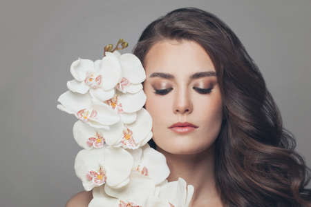 Young pretty model woman with white orchids portrait