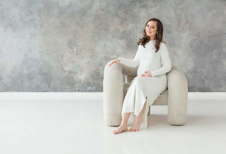 Perfect pregnant woman resting on white comfortable armchair on gray banner background with copy space