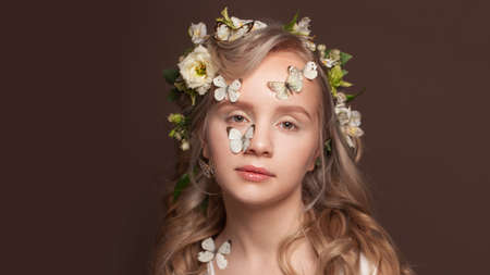 Beauty fashion portrait of young woman with healthy blonde curly hairstyle, white spring flowers and butterfly on brown banner background