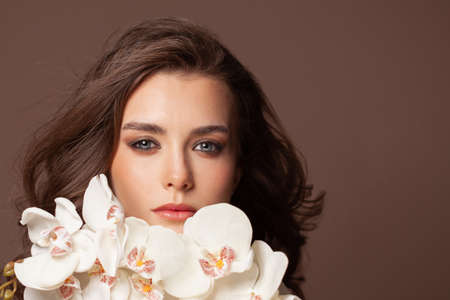Beautiful woman face with white orchid flowers portrait