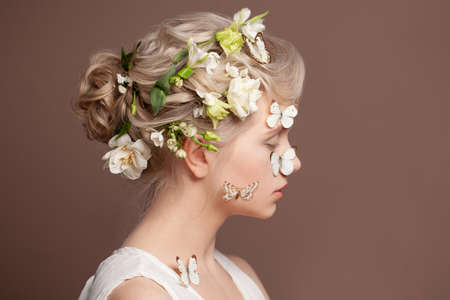 Spring young beautiful woman concept. Blonde female model with spring flowers in her healthy hair and butterfly on her clear skin on brown background