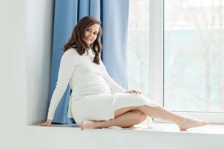 Beautiful pregnant woman sitting near window Reklamní fotografie