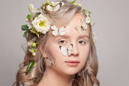 Beautiful young woman blonde model with healthy hair, white spring flowers and butterfly on white background