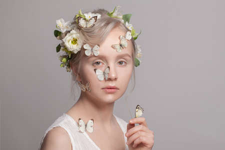 Spring beauty portrait. Cheerful young woman blonde model with spring flowers and butterfly on white. Beautiful face close up
