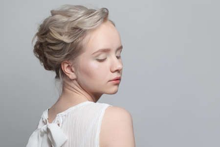 Pretty blonde woman with updo hairstyle on white background Reklamní fotografie