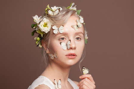 Portrait of lovely blonde woman with perfect updo hairstyle, white spring flowers and butterfly on brown background