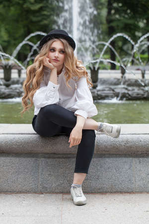 Nice woman student sitting outdoors Standard-Bild