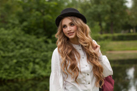 Young happy woman student in black hat outdoors