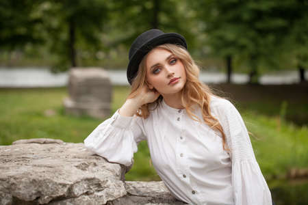 Young perfect woman in black hat outdoors Standard-Bild