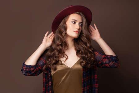 Elegant woman in plaid shirt and fedora hat posing on brown background Standard-Bild