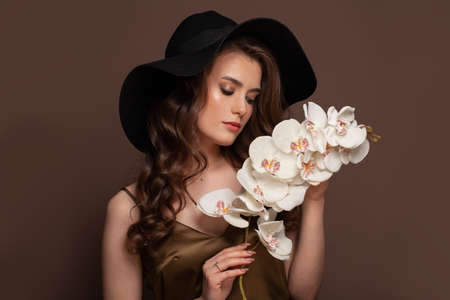 Beautiful woman with long dark healthy curly hair in black hat holding white flowers on brown background