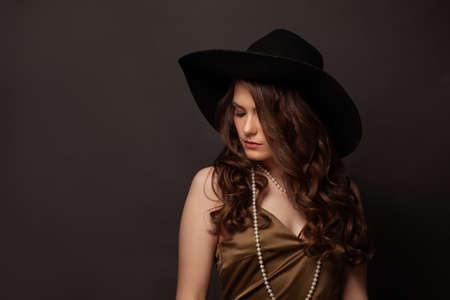 Fashionable brunette woman in black hat and pearls necklace on dark background Standard-Bild