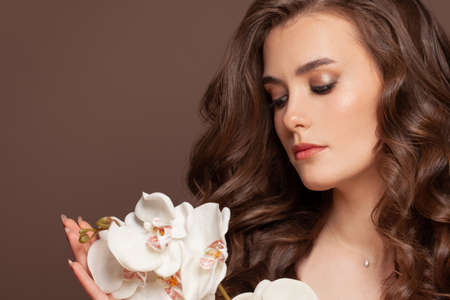Pretty female model face with healthy clear skin, brown curly hair and white orchid flowers. Facial treatment and skin care concept