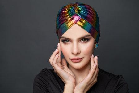 Fashion model woman in ethnic turban on head on black background Standard-Bild