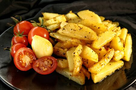 fried potatoes with crust, spices, garlic and fresh cherry tomatoes on a black plate