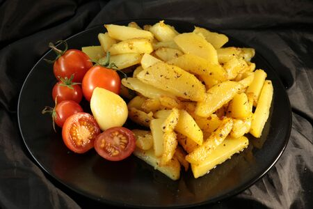 fried potatoes with spices, garlic and red cherry tomatoes on a black plate Stock fotó
