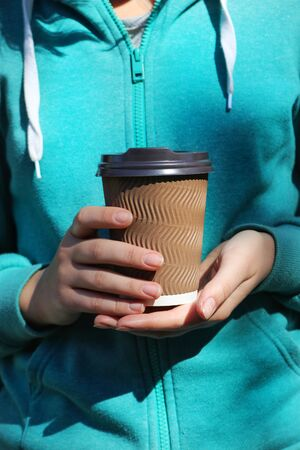 The hands of the girl in the turquoise sports case hold a brown cardboard glass with coffee Zdjęcie Seryjne