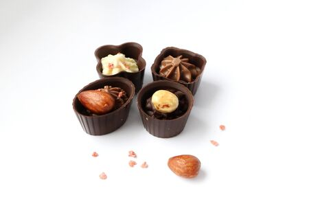 four chocolate candies with nuts on a white background Reklamní fotografie