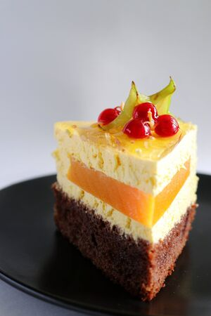 a slice of mousse cake with chocolate biscuit with a layer of mango decorated with cannon