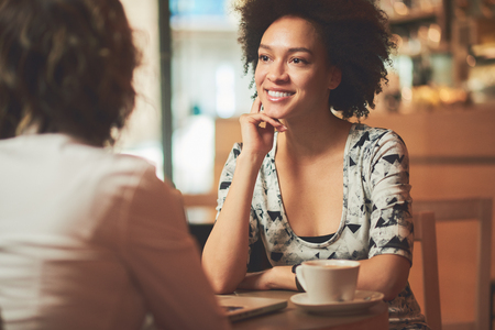 Mixed race woman in coffee shop having coffee with friend