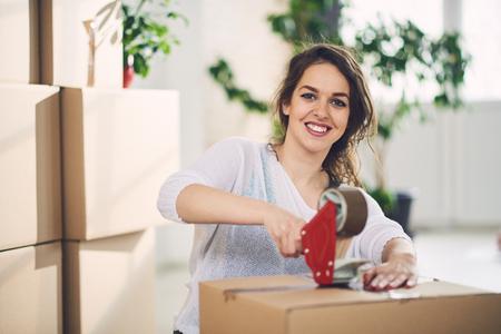 Young Caucasian girl using duct tape for packing carton boxes Stock Photo
