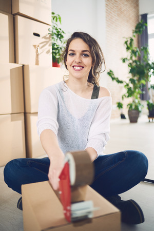 taping: Young Caucasian girl using duct tape for packing carton boxes Stock Photo