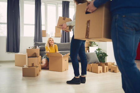 Couple relocating boxes in new apartment unpacking things Stock Photo