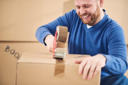 jeune homme caucasien utilisant ruban adhésif pour les trucs d & # 39 ; emballage dans la boîte