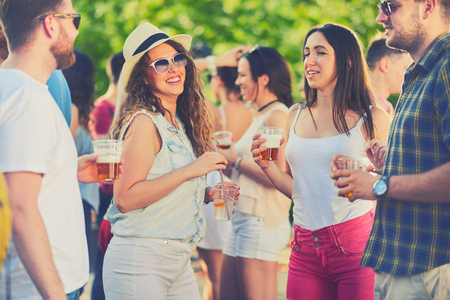 Friends chatting and having good time while standing and drinking alcohol at outdoor party and drinking beer at outdoor partymusic festival