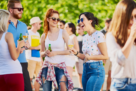 Friends chatting and having good time while standing and drinking alcohol at outdoor party