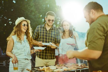 Kleine groep vrienden die alcohol drinken en een maaltijd nuttigen op een barbecuefeest
