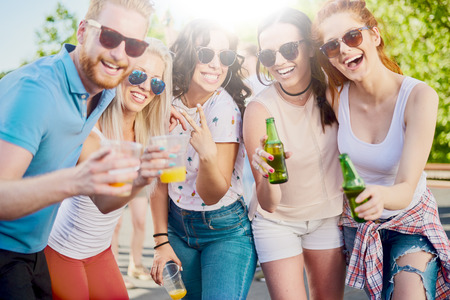 Friends posing at outdoor party while standing and drinking alcohol Stock Photo