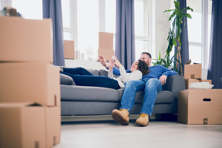 moving box: Couple sitting on sofa in new apartment and using smartphone Stock Photo